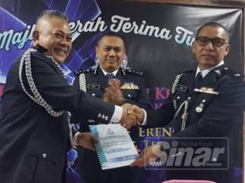 Aidi (tengah) menyaksikan Majlis Serah Terima Tugas Ketua Polis Kemaman antara Mohd Said (kiri) dan Mohd Haki.