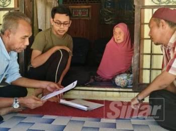 Mohamad Lukman (dua dari kiri) bersama neneknya ketika menerima kunjungan Wan Hassan (kiri) hari ini.