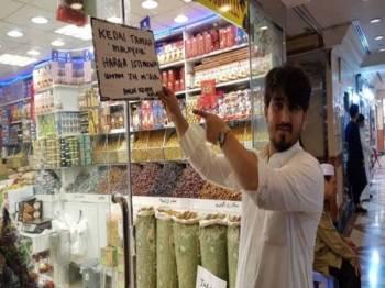 Jurujual kedai menjual tamar dan manisan Mustaffa, 25, berketurunan Arab-Pakistan yang mampu berbahasa Malaysia dan 'kecek Kelate' menunjukkan kedai dikenali dengan nama panggilan 'Kedai Tamar Malaysia' terletak di Hotel Al Haram, Madinah. Foto: Bernama