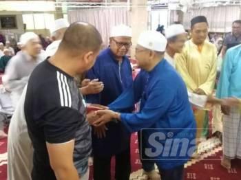 Mujahid (kanan) menyantuni bakal jemaah haji Parlimen Parit Buntar yang bakal berangkat ke Mekah pada minggu hadapan.