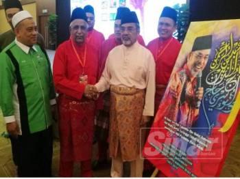Tajuddin (kanan) bersalaman dengan Musa selepas merasmikan Persidangan Perwakilan UMNO Bahagian Bukit Mertajam pagi tadi.