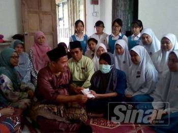 Zalikha (tengah) menerima kunjungan dan sumbangan dari SDAHA yang disampaikan oleh Hamid di rumahnya di Kampung Parit Semerah, semalam.