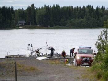 Bot pasukan kecemasan membawa serpihan pesawat kecil yang terhempas di Umea, Sweden semalam ke sebuah pelabuhan kecil. - Foto AFP