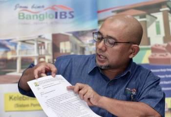 Muhamad Khanafi menunjukkan surat kelulusan yang diberikan oleh kerajaan Indonesia bagi projek pembinaan rumah anti gempa di Lombok.