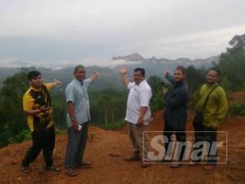 Mohd Zaid (dua dari kanan), Mansor (tiga dari kanan) dan pengunjung menunjukkan banjaran Gunung Pulai dan Baling yang boleh dilihat dari puncak Bukit AA.