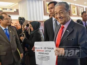 Perdana Menteri, Tun Dr Mahathir Mohamed memegang poster 'Belia18-20 tahun berhak untuk mengundi' di Parlimen hari ini. - Foto SHARIFUDIN ABDUL RAHIM