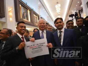 Bekas Perdana Menteri yang juga Ahli Parlimen Pekan, Datuk Seri Najib Abdul Razak memegang poster had umur mengundi di lobi Parlimen di sini hari ini. - Foto SHARIFUDIN ABDUL RAHIM