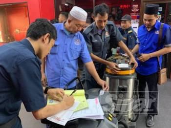 Anggota penguat kuasa MBJB memeriksa barangan di premis berkenaan yang nyaris disita kerana tidak membayar tunggakan harta semalam.