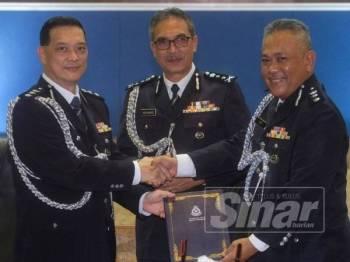 Thiew Hock Poh (kanan) menyerahkan tugas Ketua Polis Daerah Seremban kepada Mohd Said Ibrahim sambil diperhatikan Mohamad (tengah).