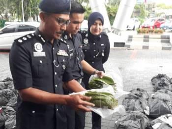Mohd Rozi (dua dari kiri) menunjukkan daun ketum yang berjaya dirampas pasukan perondanya di Jalan Derang, Pokok Sena semalam.