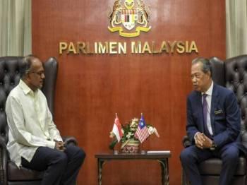 Menteri Dalam Negeri Tan Sri Muhyiddin Yassin (kanan) berbincang dengan rakan sejawatnya K Shanmugam ketika menerima kunjungan hormat Menteri Dalam Negeri Singapura itu di Bangunan Parlimen hari ini.- Foto Bernama