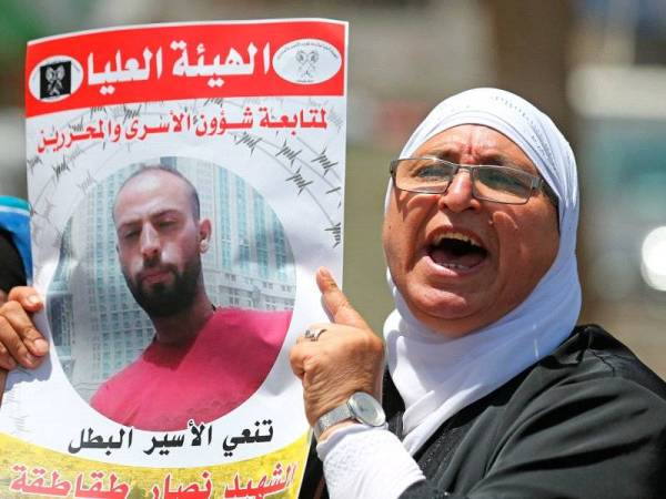 Seorang wanita Palestin menyertai protes menuntut siasatan ke atas kematian Nassar.