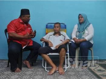 Norhisham (tengah) bersama isterinya sewaktu menerima kunjungan Mohd Hamidi.