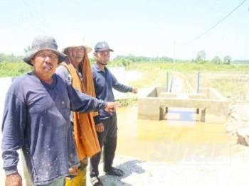 Harun (kiri) bersama rakan-rakannya mengharapkan ihsan pihak berkenaan supaya segera menyiapkan projek longkang yang terbengkalai.