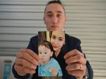 Sadam Abdusalam memegang gambar isterinya, Nadila Wumaier dan anak lelaki mereka Lutifeier. -  Foto AFP