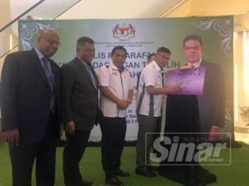 Saifuddin menandatangani plak Penarafan Zon Perdagangan Terpilih di pusat beli-belah Komtar JBCC Mall, di sini hari ini.