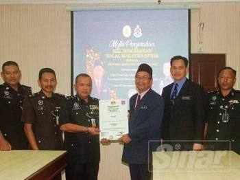 Wan Sani (tiga kiri) menerima Sijil Pengesahan Halal Malaysia disampaikan Mohd Azam.
