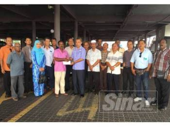 Ahmad Suzaimie (tujuh dari kanan) menyerahkan Faedah Hilang Upaya Sementara kepada Murugasu di Terminal Bas dan Teksi Kluang.