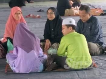 Dr Samsuri (kanan) duduk bersila di atas tikar sambil mendengar kuliah dhuha disampaikan presiden Pas di Rusila hari ini.