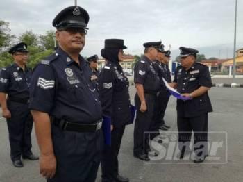 Muhd Nurhishamuddin (kanan) bertanyakan sesuatu kepada salah seorang anggota yang menerima kenaikan pangkat pada majlis tersebut.