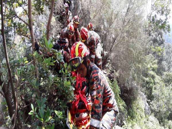 Anggota bomba ketika membawa mangsa turun dari puncak bukit. - FOTO JBPM SELANGOR