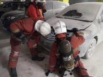 Pasukan bomba memadamkan kebakaran pada sebuah kereta di tempat parkir. - Foto IHSAN BOMBA