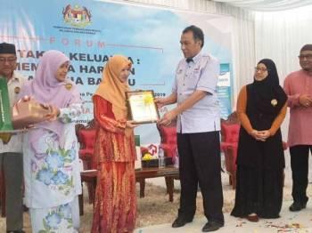 Husam (empat, kanan) menyampaikan sijil kepada salah seorang wanita yang cekal membesarkan anak-anak sempena Hari Ibu Bapa Kelantan, hari ini. - Foto IHSAN FB HUSAM MUSA