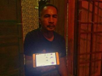 Mohd Nasir menunjukkan gambar anak saudaranya, Shahril Apipie ketika ditemui di rumahnya di Kampung Cabang Empat Tok Uban.