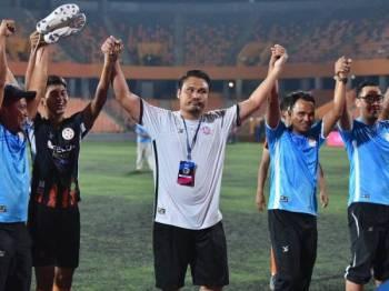 Mohd Nidzam (tengah) meraikan kejayaan Felda United kekal di Liga Super. Foto - MFL
