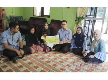 Mohd Azran menyerahkan baucer kepada Azliana dalam kunjungan berkenaan.