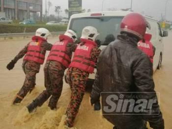 Anggota bomba membantu mengalihkan beberapa buah kenderaan yang terperangkap dalam banjir kilat di Jalan Rawang menghala Batu Arang di sini petang tadi.