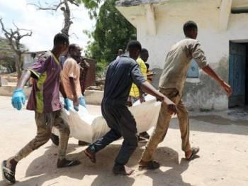 Mayat seorang penduduk awam yang terbunuh dalam letupan di luar sebuah hotel di Mogadishu, Somalia hari ini diangkat oleh orang ramai. - Foto Reuters