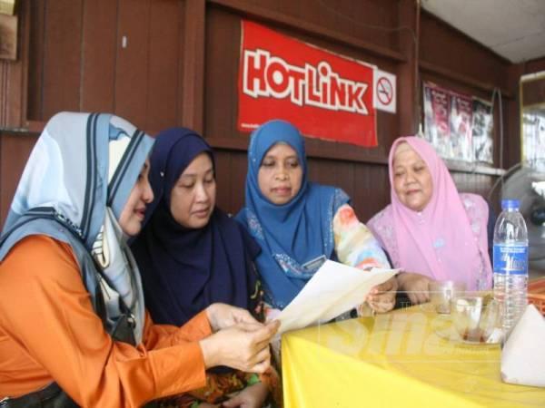 Noraida (dua dari kiri) ditenangkan rakan-rakan sekerja termasuk Rosita (kiri).