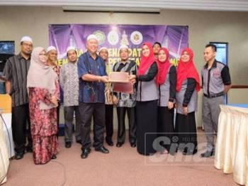 Saiful Azmi (enam dari kiri) dan Mohammad Syukri melihat pertukaran dokumen antara Kohijrah dan Kitab pada majlis menandatangani MoU di KGRP Kerteh.