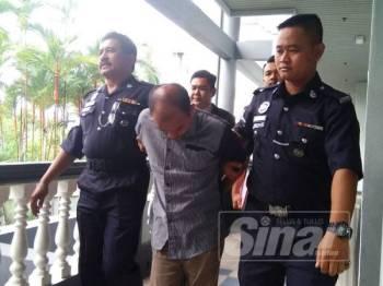Zainal Abidin diiringi anggota polis ketika dibawa keluar dari Mahkamah Sesyen di sini, hari ini.