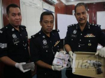 Abdullah (kanan) menunjukkan pistol dan wang tunai yang dirampas di rumah sewa keluarga warga Thailand.