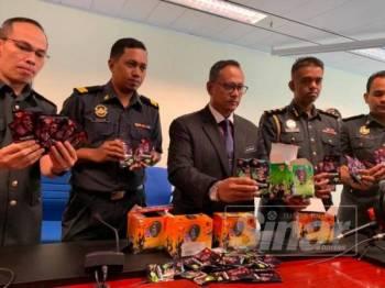 Mohd Hairul (tengah) menunjukkan gula-gula Ghost Smoke yang dirampas dalam operasi berkenaan.