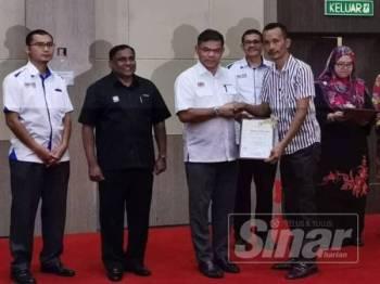Saifuddin (tiga dari kiri) menyerahkan watikah Penyelaras Kepenggunaan Parlimen kepada individu yang dilantik.