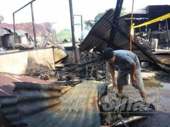 Salah seorang mangsa kebakaran, Mohd Arif Fikri Abd Rahman melihat keadaan motosikalnya yang terbakar di Kampung Melayu, Kluang.