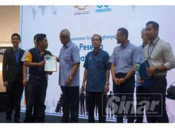 Mahfuz (empat dari kiri) menyerahkan surat penghargaan kepada peserta Program Penempatan Pekerjaan Semula Perkeso, Mohd Amirul Amran (tiga dari kiri) pada Karnival Pekerjaan EIS Perkeso Kedah 2019 di Aman Sentral hari ini.