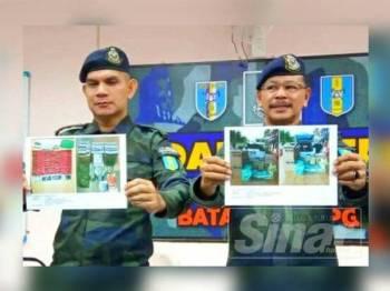 Ab Aziz (kanan) menunjukkan gambar barangan yang dirampas pada sidang media di Markas Taktikal Batalion 8 PGA Lubok Setol, Rantau Panjang hari ini.