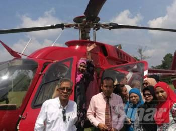 Zahara melambai tangan kepada rakan-rakan dan murid sebelum menaiki helikopter sambil diperhatikan Mokhtar (berdiri dari kiri).