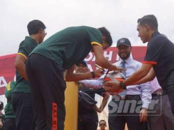 Mohd Fadzrul menandatangani bola untuk dihadiahkan kepada penyokong Hijau Kuning pada Majlis Perarakan dan Sambutan Kemenangan Shoppe Piala FA 2019 di Dataran Wisma Darul Aman, di sini hari ini.