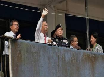 Menteri Dalam Negeri Tan Sri Muhyiddin Yassin (dua, kiri) melambai tangan ke arah penghuni Kompleks Perumahan Ibu Pejabat Polis Diraja Malaysia Kontinjen Sarawak ketika melawat kompleks perumahan berkenaan hari ini. - Foto Bernama