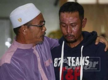Abdul Rahim (kiri) menenangkan Hairol yang sebak menerima sumbangan hasil kutipan orang ramai.