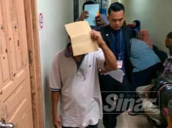 Ibrahim (baju putih) ketika keluar daripada kamar perbicaraan, di Mahkamah Majistret Johor Bahru di sini hari ini.