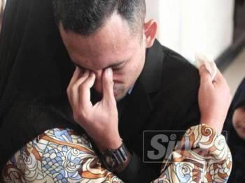 Muhammad Akmal tidak dapat menahan sebak lalu memeluk ibunya selepas Mahkamah Tinggi Kuala Lumpur hari ini memutuskan dia dilepas dan dibebaskan daripada pertuduhan terlibat dengan kematian Zulfarhan Osman. - Foto ZAHID IZZANI