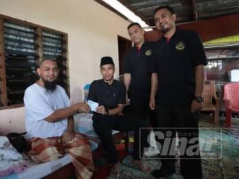 Baddrol (dua dari kiri) menyerahkan bantuan kepada Zulkarnain Md Yusoff (kiri) ketika ditemui di kediamannya Kampung Titi Teras di sini hari ini.