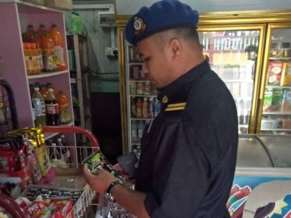 Penguatkuasa KPDNHEP Terengganu memeriksa premis bagi mengesan penjualan gula-gula 'Ghost Smoke'. -Foto KPDNHEP