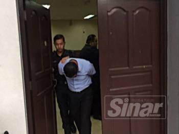Abdul Munif ketika dibawa keluar dari mahkamah seksyen di sini, hari ini.